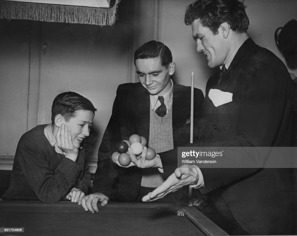 English boxer Freddie Mills (1919 - 1965, right) shows Jack Carney and Colin Smith (left) his trick of holding 12 snooker balls in one hand at the semi-finals of the boys' billiards championship at Burroughes Hall, London, 2nd January 1948. Carney, from Pontardawe in Wales, won the match to enter the final.