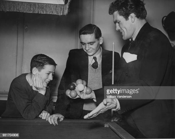 English boxer Freddie Mills shows Jack Carney and Colin Smith his trick of holding 12 snooker balls in one hand at the semifinals of the boys'...