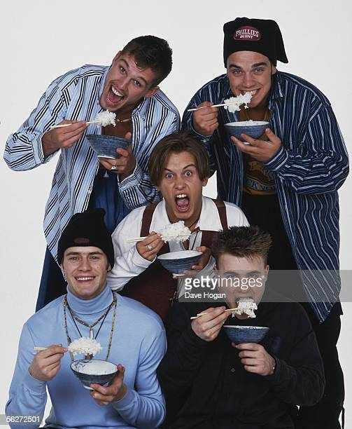 English boy band Take That eating rice with chopsticks circa 1995 From left to right Jason Orange and Robbie Williams Mark Owen Howard Donald and...