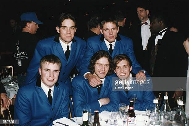 English boy band Take That wearing matching blue teddy boy suits at the Brit Awards where they performed a medley of Beatles songs 1994 From left to...