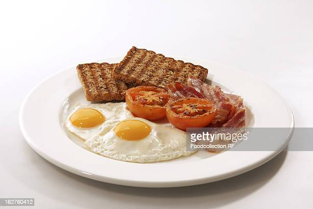 English breakfast with fried egg, bacon, tomatoes, mushrooms and toast on plate
