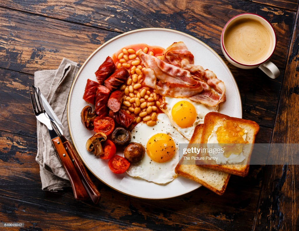 English breakfast with fried eggs, sausages, bacon, beans, toasts and coffee on wooden background : Stock Photo