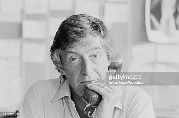 English broadcaster and author Michael Parkinson pictured holding a telephone receiver in his office in London on 27th August 1980