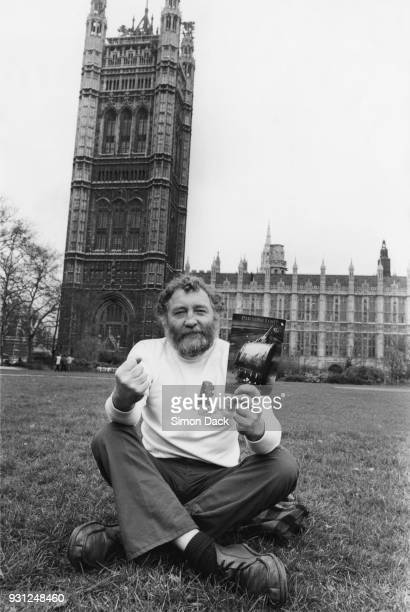 English broadcaster and environmentalist David Bellamy sits in Parliament Square with a copy of 'Paradise Lost' the Friends of the Earth report on...