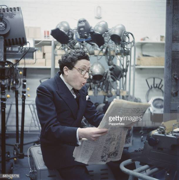 English broadcaster and journalist Bernard Levin studies a newspaper on the set of the BBC satirical television series 'That Was the Week That Was'...