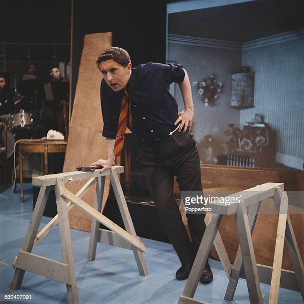 English broadcaster and journalist David Frost performs in a DIY sketch on the set of the BBC satirical television series 'That Was the Week That...