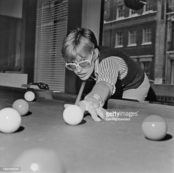 English broadcaster and journalist Janet Street-Porter, fashion editor of the Evening Standard newspaper, during a game of snooker, UK, 5th August...