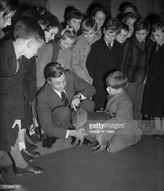 English broadcaster and naturalist David Attenborough intoduces an audience of children including six yearold Michael Webb to a capybara at the Royal...