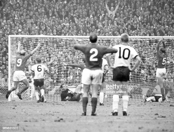 English brothers Bobby and Jack Charlton along with Martin Peters throw their arms in the air after overcoming the German defence and scoring the 21...