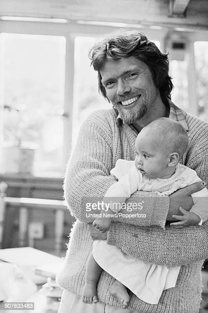 English businessman and owner of Virgin Records Richard Branson pictured holding a baby on his houseboat on the Grand Union canal in London on 26th...
