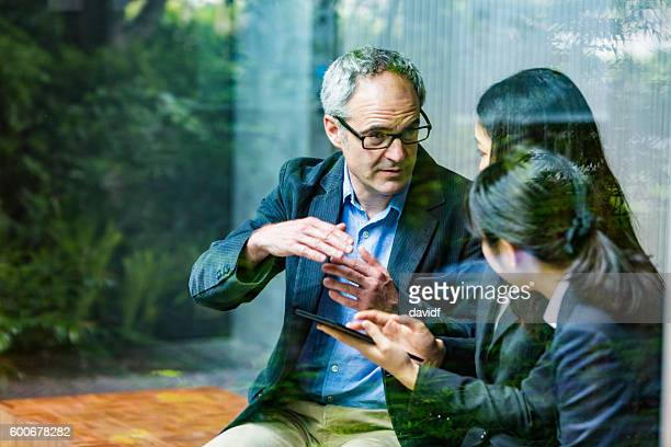 english businessman working advising japanese corporate professional business women - customs stock pictures, royalty-free photos & images