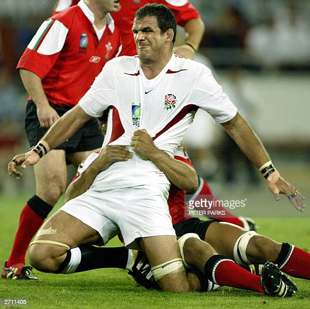 English captain and lock Martin Johnson reacts during a tackle by Welsh captain and flanker Colin Charvis during their quarter-final Rugby World Cup...