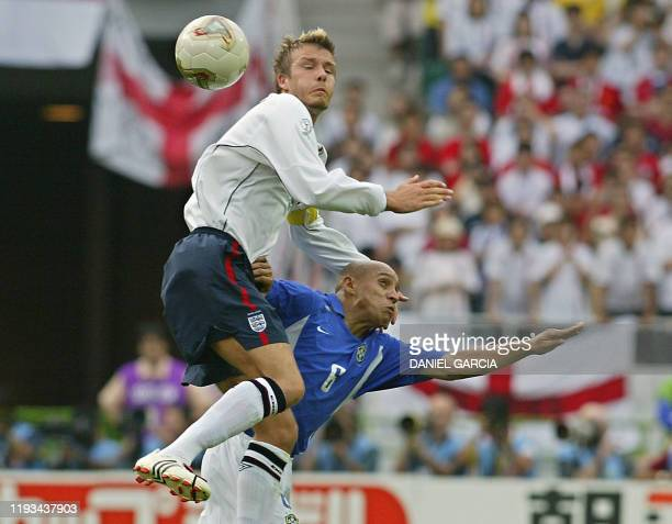 English captain and midfielder David Beckham heads off the ball in front of Brazilian defender Roberto Carlos during the England/Brazil quarterfinal...