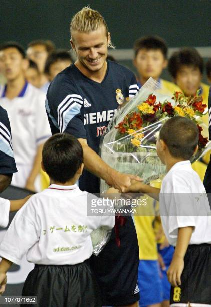 English captain David Beckham of Real Madrid is welcomed by Japanese children before a team training session in Tokyo, 03 August 2003. Members of...