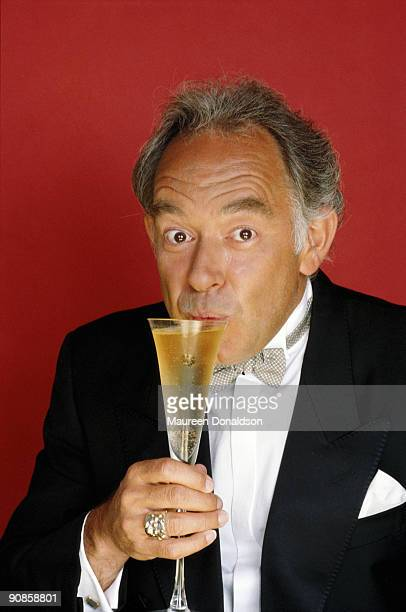 English celebrity writer Robin Leach sips a glass of champagne, circa 1990. He hosted the television show 'Lifestyles of the Rich and Famous' in the...