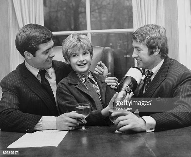 English child actor Mark Lester pours champagne for boxing champion Johnny Cheshire who is signing a contract with manager John Daly 28th November...