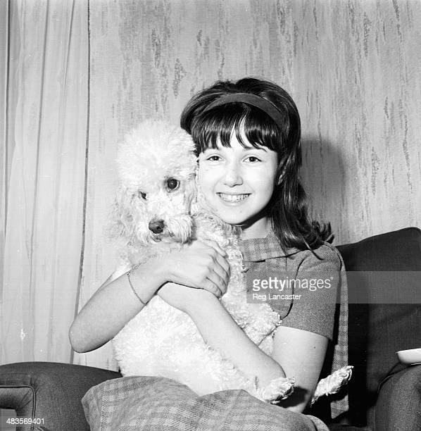 English child actress Adrienne Poster holding a poodle 28h November 1963