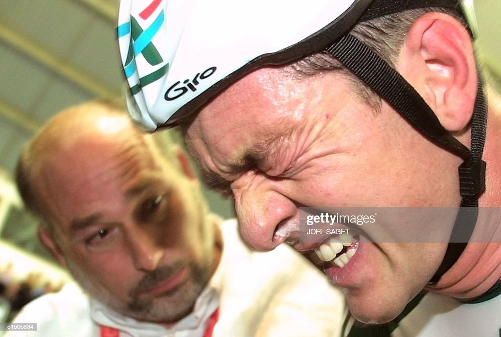 English Chris Boardman grimaces as his coach Michel Docok (L) looks at him after setting a new one-hour World Record at 49.441 kms on the track of Manchester during the 2000 World Track Cycling Championships 27 October 2000. Belgian Eddy Merckx was the best rider with 49.431kms setting in 1972 in Mexico.