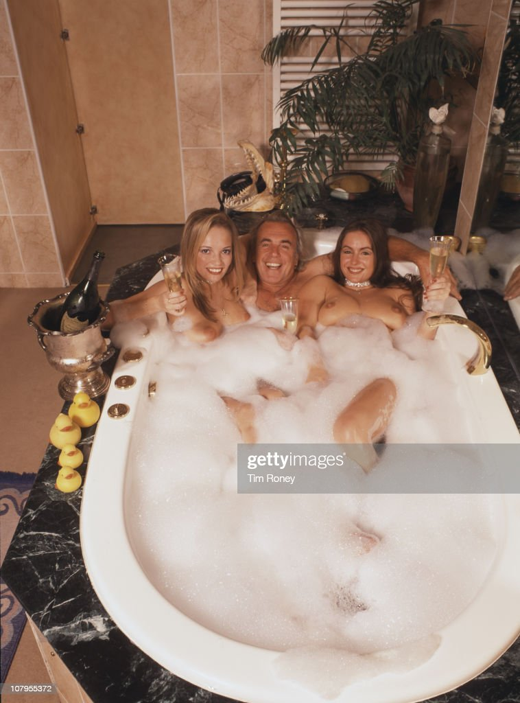 English club owner Peter Stringfellow sharing a bath with two lady friends, circa 1990.