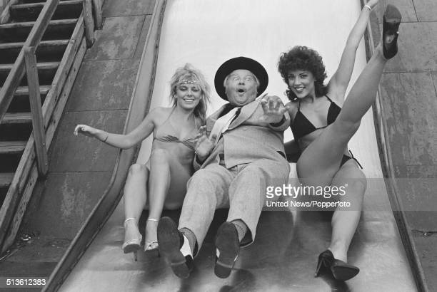 English comedian and actor Benny Hill pictured on a slide with two female models wearing bikinis in London on 14th September 1983