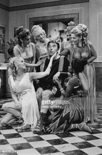 English comedian and actor Frankie Howerd and costars on the set of the BBC TV sitcom 'Up Pompeii' 7th September 1970 Howerd plays the slave Lurcio...