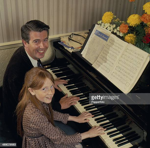 English comedian and host Leslie Crowther posed at the piano at home with his daughter actress Liz Crowther in 1967