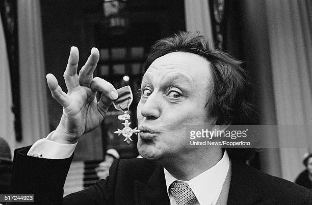 English comedian and singer Ken Dodd pictured holding his OBE following an investiture at Buckingham Palace in London on 19th February 1982