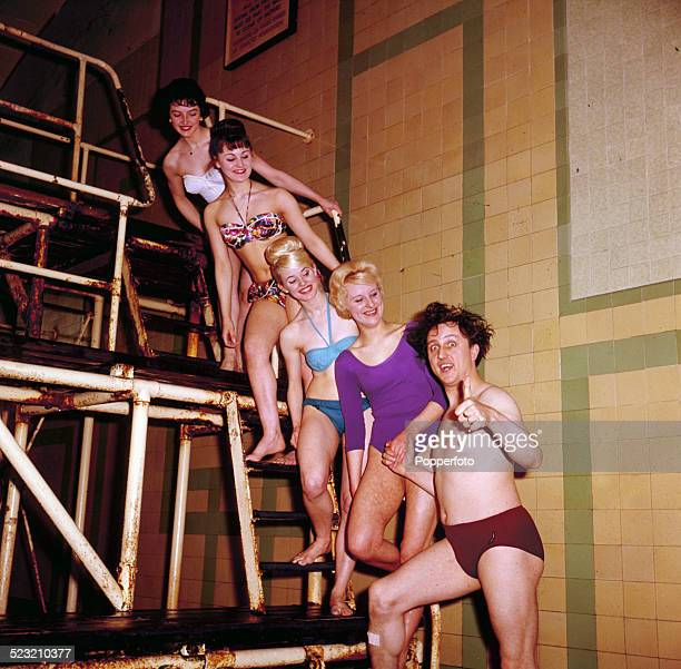 English comedian and singer Ken Dodd pictured wearing swimming trunks posing with four young girls in swimwear beside a swimming pool in 1963