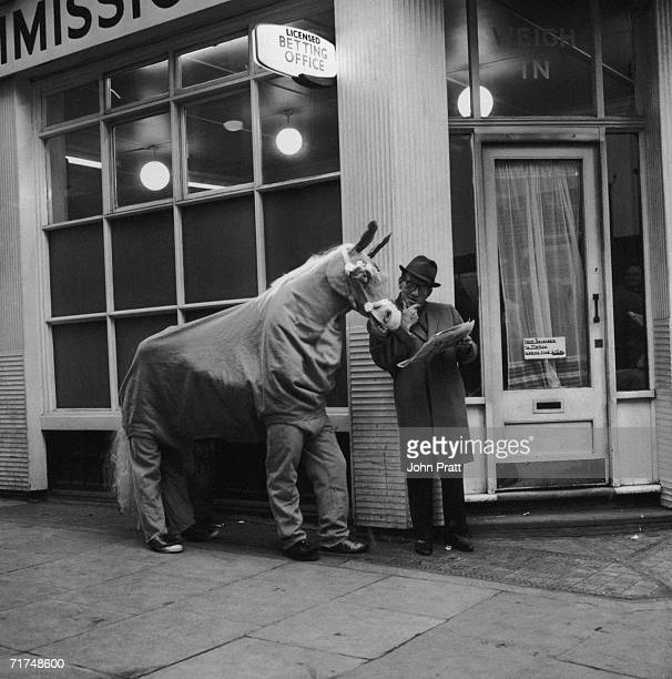 English comedian Arthur Askey studies form with Neddy the pantomime horse outside a licensed betting office during rehearsals for the Christmas show...