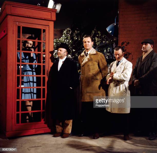 English comedian Arthur Haynes pictured wearing a black coat with English actor Nicholas Parsons queuing outside a telephone box waiting to make a...