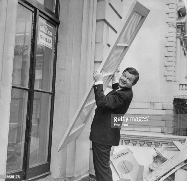 English comedian Benny Hill helping with building work on his flat in Kensington London 20th February 1967