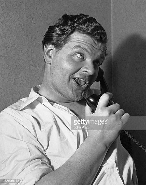 English comedian Benny Hill makes a phone call during a morning off at his new flat in Maida Vale London 15th August 1955 He is currently appearing...