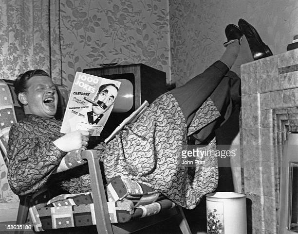 English comedian Benny Hill reading a joke book during a morning off at his new flat in Maida Vale London 15th August 1955 He is currently appearing...