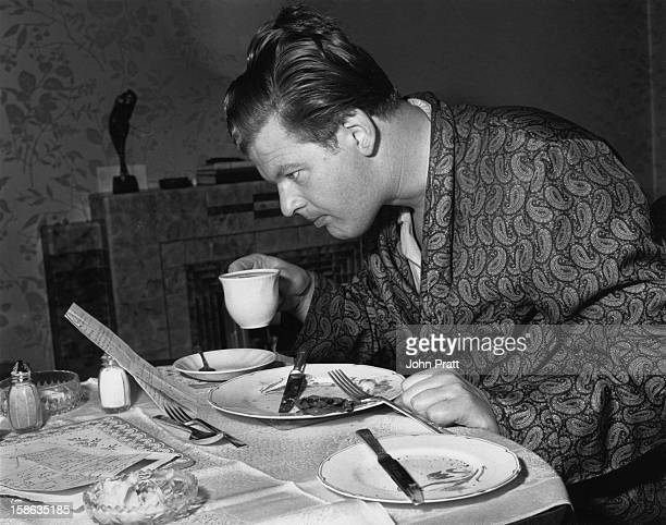 English comedian Benny Hill reads his mail over breakfast at his new flat in Maida Vale London 15th August 1955 He is currently appearing in 'Paris...