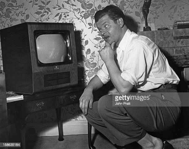 English comedian Benny Hill waits for his television to warm up during a morning off at his new flat in Maida Vale London 15th August 1955 He is...