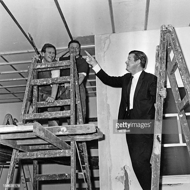 English comedian Benny Hill with two workmen who are combining Hill's flat with the one next door Kensington London 20th February 1967