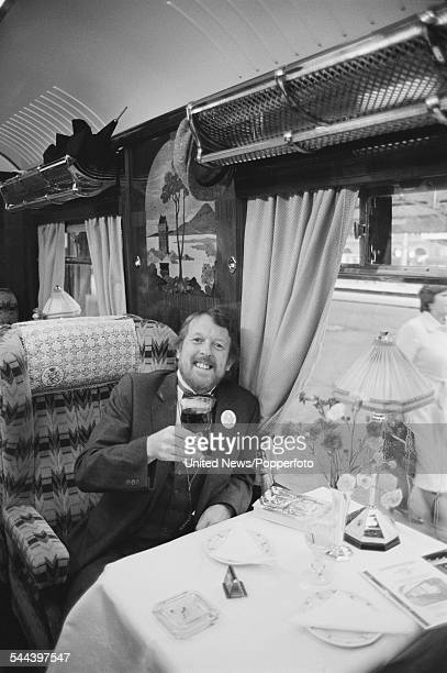 English comedian cartoonist and actor Willie Rushton pictured holding a glass of wine whilst sitting in an armchair in a Pullman carriage on the...