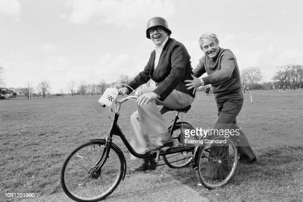 English comedian Eric Morecambe driving a tricycle while fellow English comedian Ernie Wise pushes him UK 27th March 1980