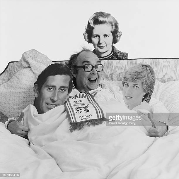 English comedian Eric Morecambe in bed with cutouts of Prince Charles Diana Princess of Wales and Margaret Thatcher 8th February 1982 He is wearing a...