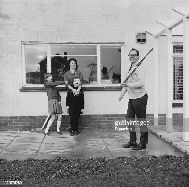 English comedian Eric Morecambe pictured marching with a replica rifle as his wife Joan Bartlett and children Gail and Gary look on with amusement at...