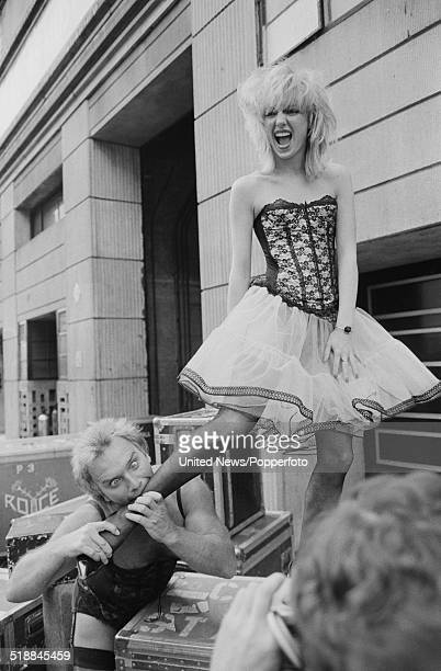 English comedian Freddie Starr attempts to bite the ankle of a member of dance troupe Hot Gossip at a press event to launch his upcoming theatre tour...