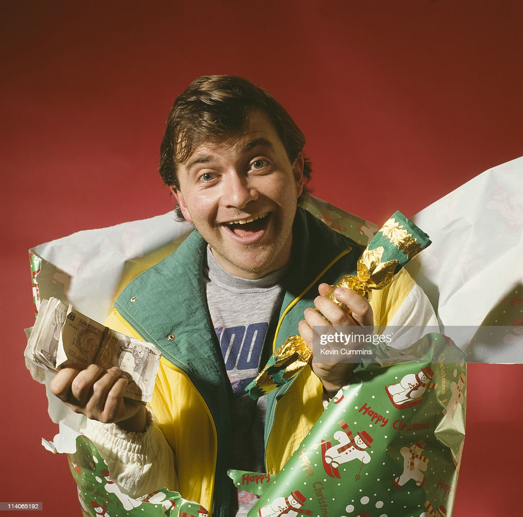 English comedian Harry Enfield emerges from a christmas cracker at a photoshoot circa 1992.