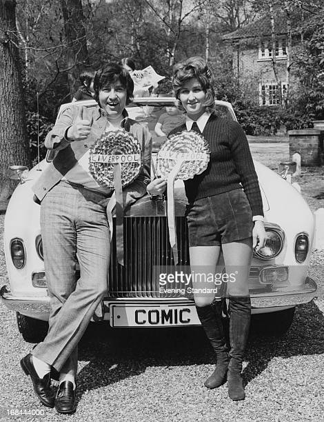 English comedian Jimmy Tarbuck and his wife Pauline leaning on the bonnet of his Rolls Royce May 1971 Both are wearing outsize Liverpool Football...