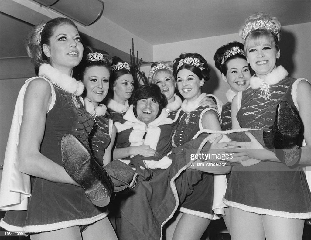 English comedian Jimmy Tarbuck is carried by a troupe of 'Miss Christmasses' at a Variety Club of Great Britain charity lunch at the Savoy Hotel, London, 10th December 1968.