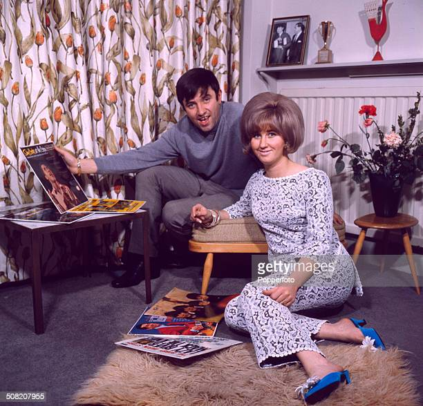 English comedian Jimmy Tarbuck pictured holding a Sam Cooke album in his hand at home with his wife Pauline in 1965