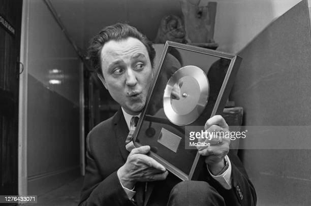 English comedian Ken Dodd with a golden disc for his hit single 'Tears', December 1965.