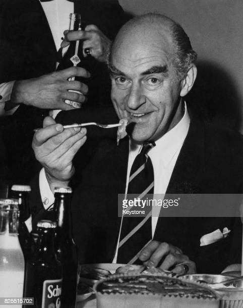 English comedian Kenneth Horne eating an oyster at the annual Colchester Oyster Feast, at the Town Hall in Colchester, England, 28th October 1960.