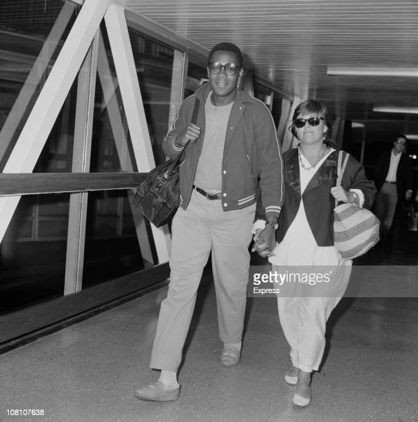 English comedian Lenny Henry and his wife comedian Dawn French at an airport 6th November 1984