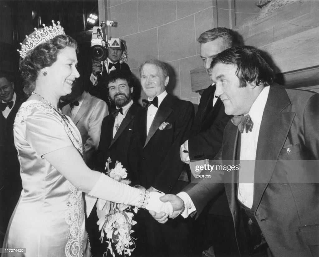 English comedian Les Dawson (1931 - 1993) shakes hands with Queen Elizabeth II at the Royal Variety Performance at the Theatre Royal, Drury Lane, 10th November 1979. In the background are American actor Red Buttons (1919 – 2006, centre) and Irish flautist James Galway (centre, left).