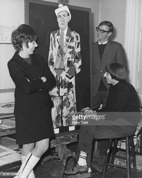 English comedian Roy Hudd and his wife Ann watch artist Barry Fantoni finish off his portrait of the late comedian Max Miller 29th November 1966 Hudd...